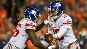 Giants quarterback Eli Manning hands off to Orleans Darkwa