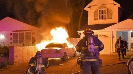 Firefighters respond to a car fire in the