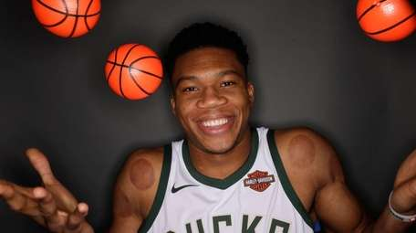 Milwaukee Bucks' Giannis Antetokounmpo juggles some small basketballs