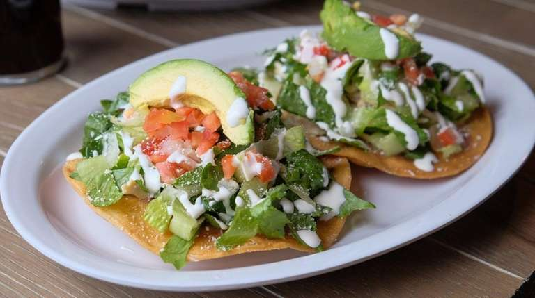 Chicken tostadas are topped with lettuce, salsa fresca