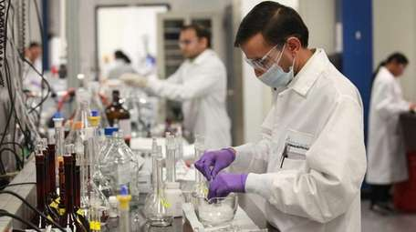 Technicians work in the laboratory at Amneal Pharmaceuticals'