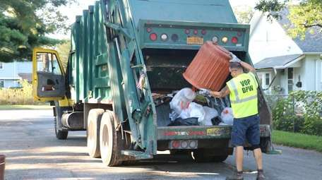 Patchogue Village sanitation worker Troy Quarltere empties a
