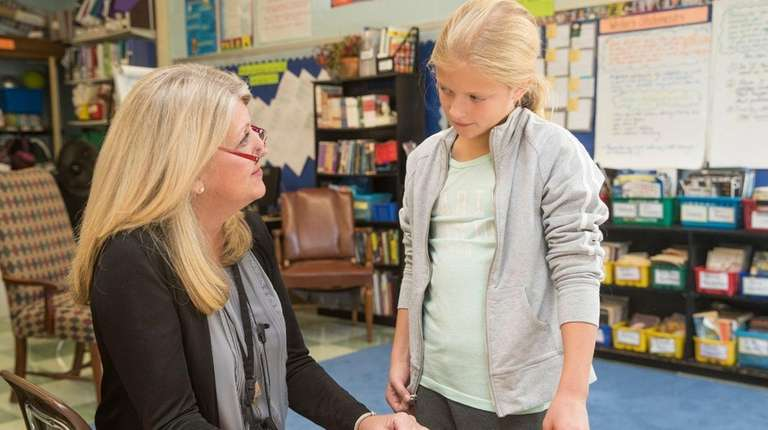 Fifth-grade teacher Kate Hunter speaks with her student