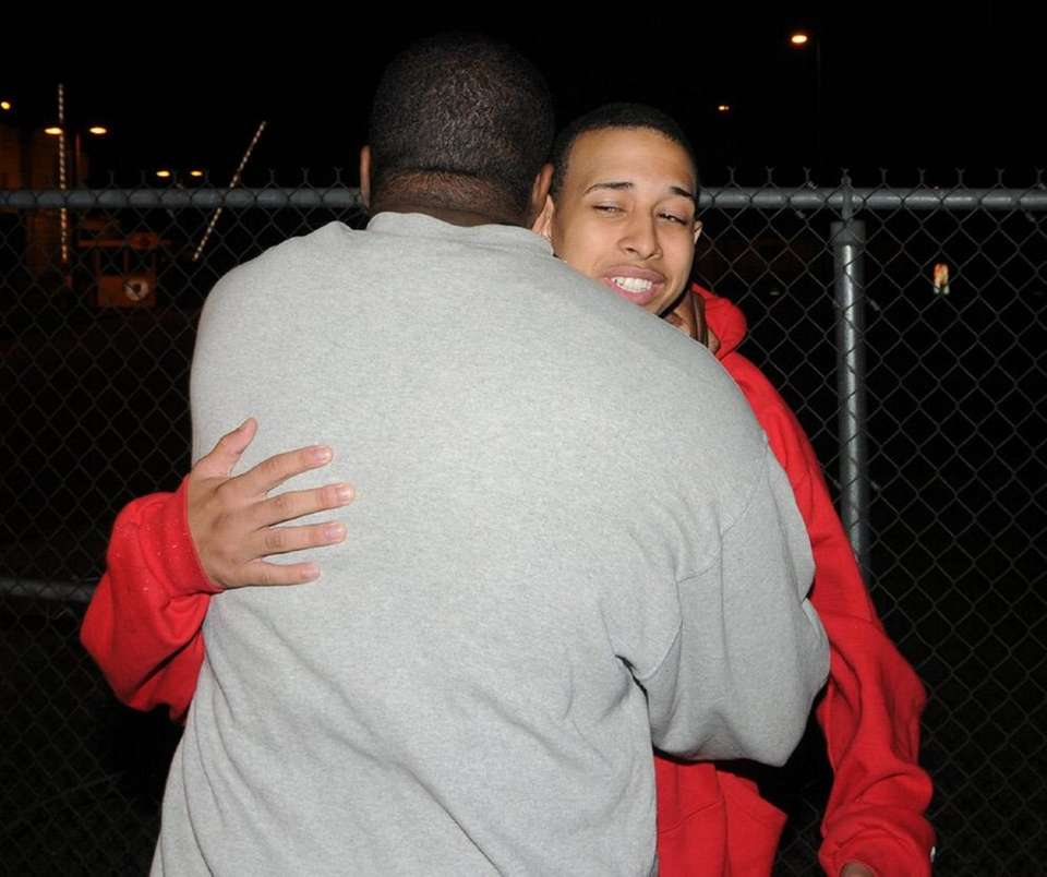 Stalin Felipe hugs Rondell Bedward outside East Meadow