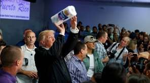 President Donald Trump tosses paper towels into a