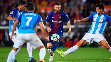 Malaga midfielder Adrian Gonzalez and defenders Juan Carlos