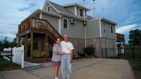 Charles and Laura Spoto stand outside their elevated