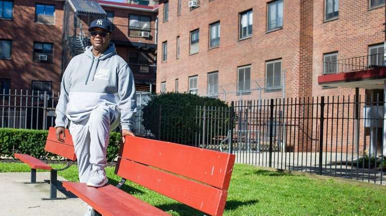 Nathaniel Gregory stands beside benches at the Moxey