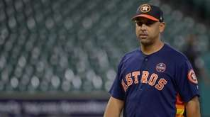 Houston Astros bench coach Alex Cora watches batting