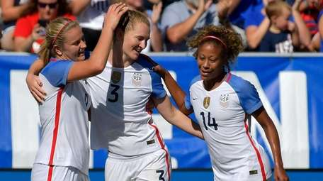 Teammates congratulate Samantha Mewis of the USA after