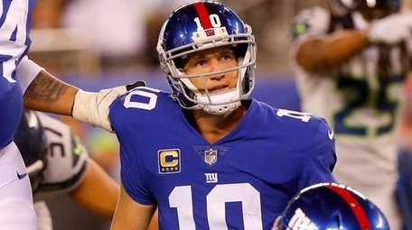 Eli Manning of the  Giants looks on with