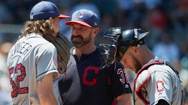 Indians pitching coach Mickey Callaway, center talks to