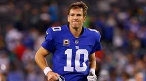 Eli Manning of the Giants runs off the