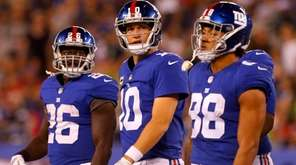 Eli Manning walks to the sidelines with Giants teammates
