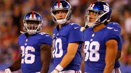Eli Manning walks to the sidelines with Giantsteammates