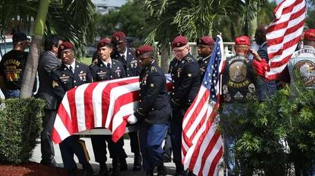U.S. Military honor guards carry the coffin of