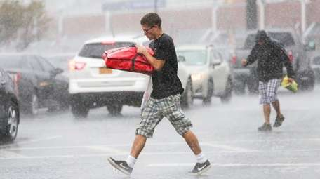 A pizza delivery man battles wind and rain