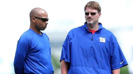 Giants general manager Jerry Reese, left,talks with head