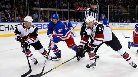 The Coyotes' Derek Stepan and Max Domi reach