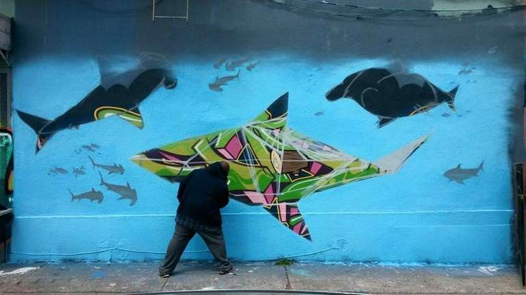 Lenny Achan paints a stylized shark as part