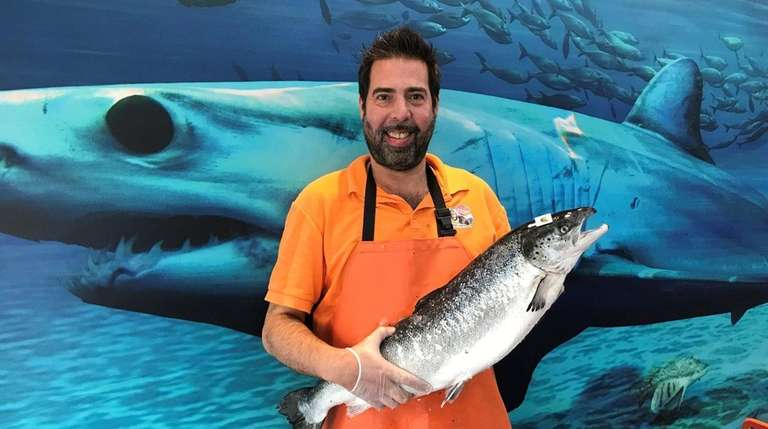 Jeffrey Drain holds Atlantic salmon, which he buys