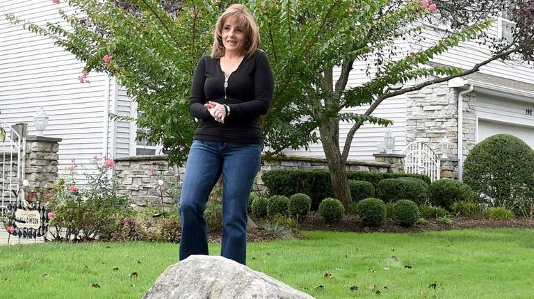 Deborah Fauci-Dardis stands beside a boulder in front