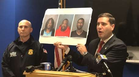 Suffolk County Police Commissioner Timothy Sini holds images