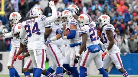 Bills players celebrate after safety Micah Hyde, center,