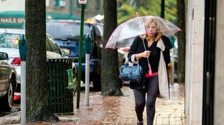 A woman with an umbrella tries to stay