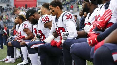 Members of the Houston Texans kneel during