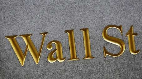 A sign for Wall Street carved into the
