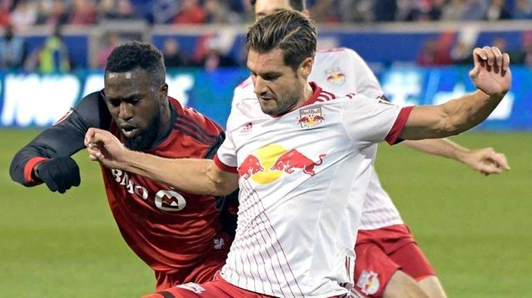Red Bulls defender Damien Perrinelle holds off Toronto