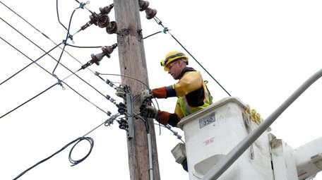 A PSEG worker repairs downed wires caused by