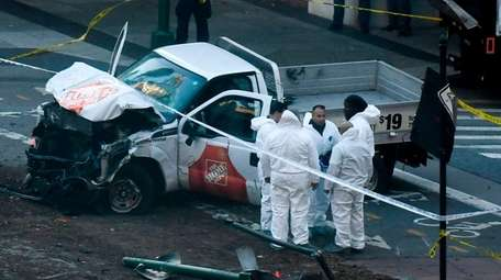 Investigators inspect a truck after it was driven