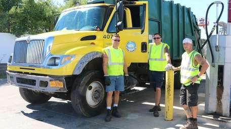 Patchogue Village sanitation workers Charlie Collins, left, Troy