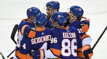 Islanders players celebrate a goal by Nikolay Kulemin