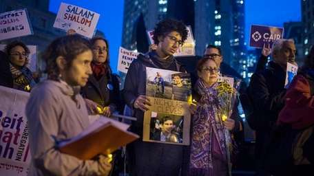Bahij Chancey, 26, center, holds a photo of