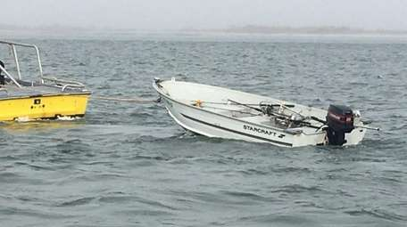 A disabled boat is towed in Moriches Inlet