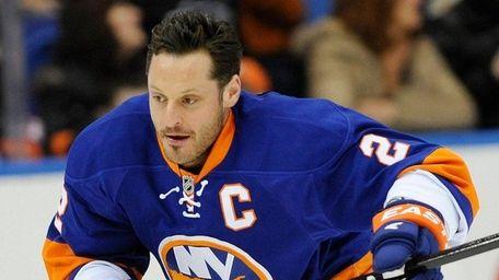 Islanders defenseman Mark Streitskates towarda puck before a