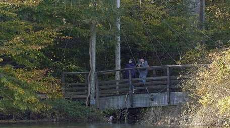 People walk on a bridge at Avalon Park