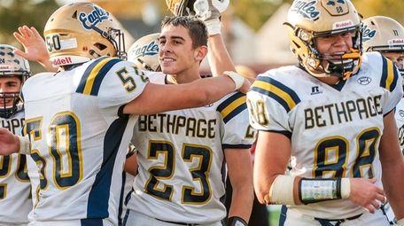 Bethpage quarterback Jason Seiter celebrates with his teammates
