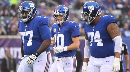 Giants quarterback Eli Manning, center, reacts after he