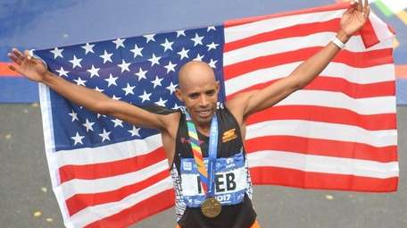 Meb Keflezighi poses for pictures carrying an American