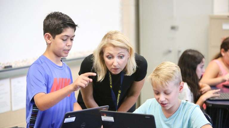 Barbara Luba helps her sixth-grade social studies students