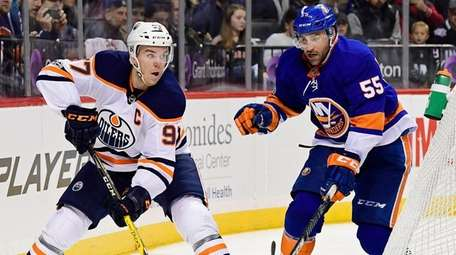 The Oilers' Connor McDavid is defended by the