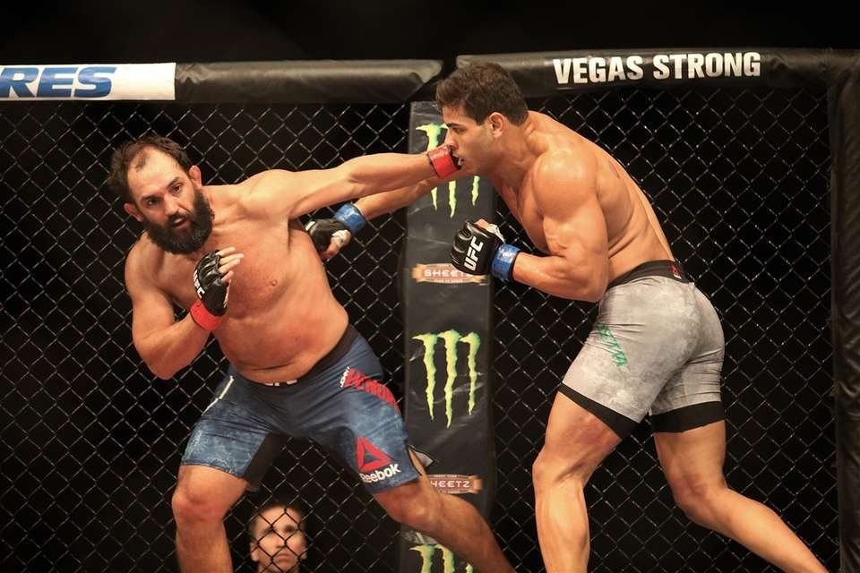 Paulo Costa, right, strikes with Johny Hendricks during