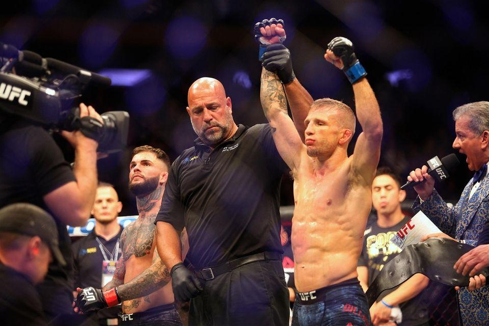TJ Dillashaw, right, celebrates as referee Dan Miragliotta