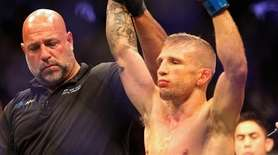 TJ Dillashaw, right, celebrates as referee Dan Miragliotta