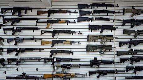 Semi-automatic rifles line a wall in a gun