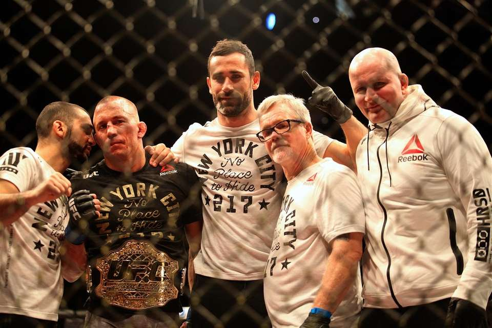 Georges St-Pierre poses with his cornermen after beating